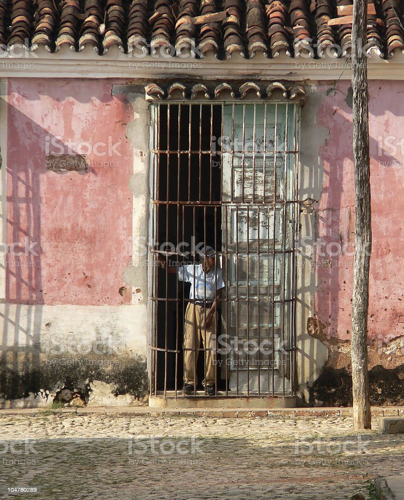 Old man looking out from his home in Trinidad, Cuba royalty-free stock photo