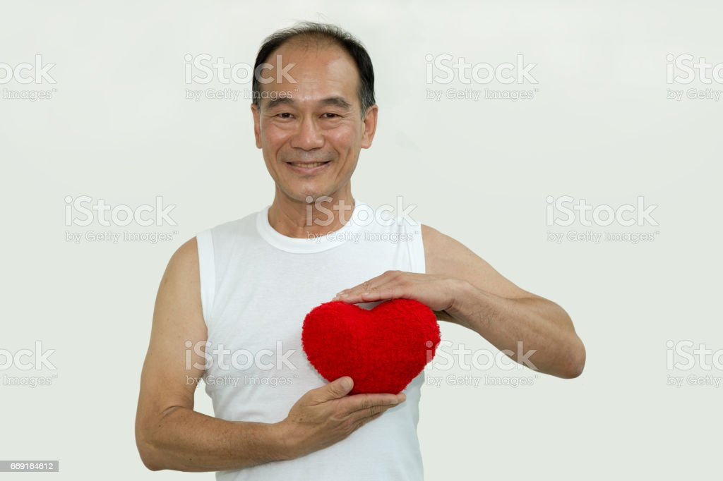 old man on whit shirt holding a red heart on white background stock photo
