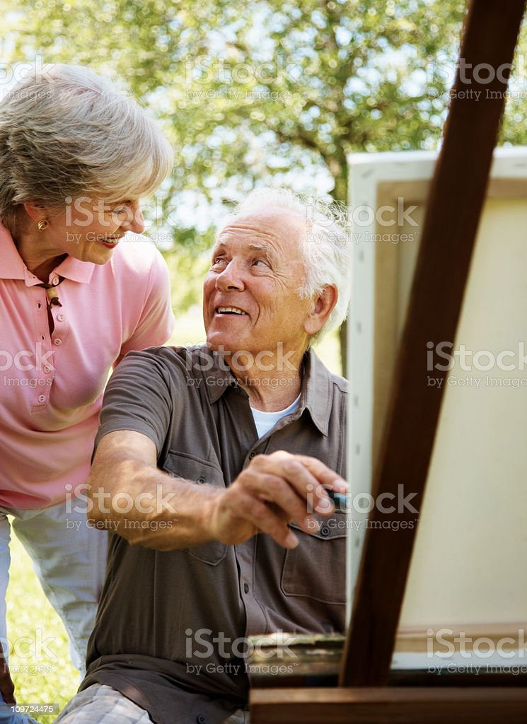 Old man painting a picture on canvas with his wife stock photo