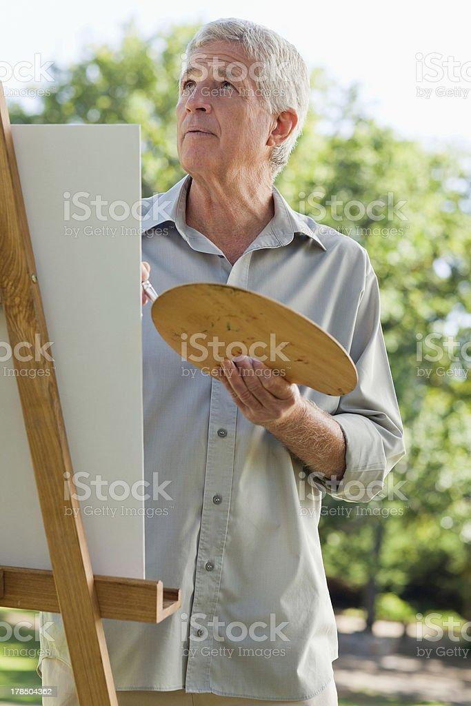 Old man painting and looks up at the sky royalty-free stock photo