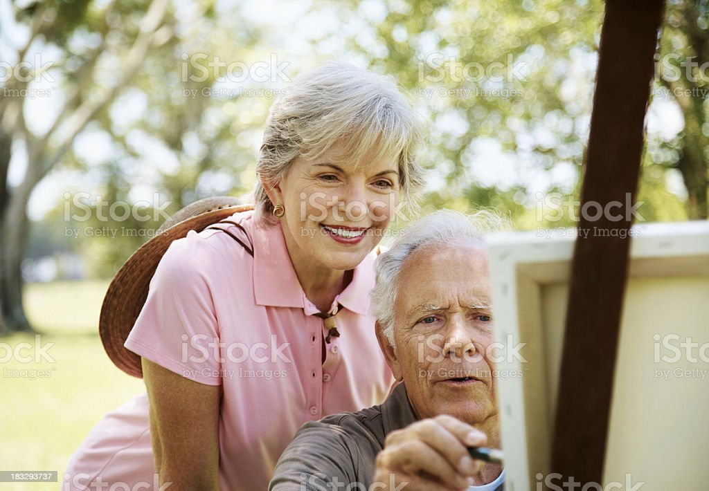 Old man painting on canvas with his wife stock photo