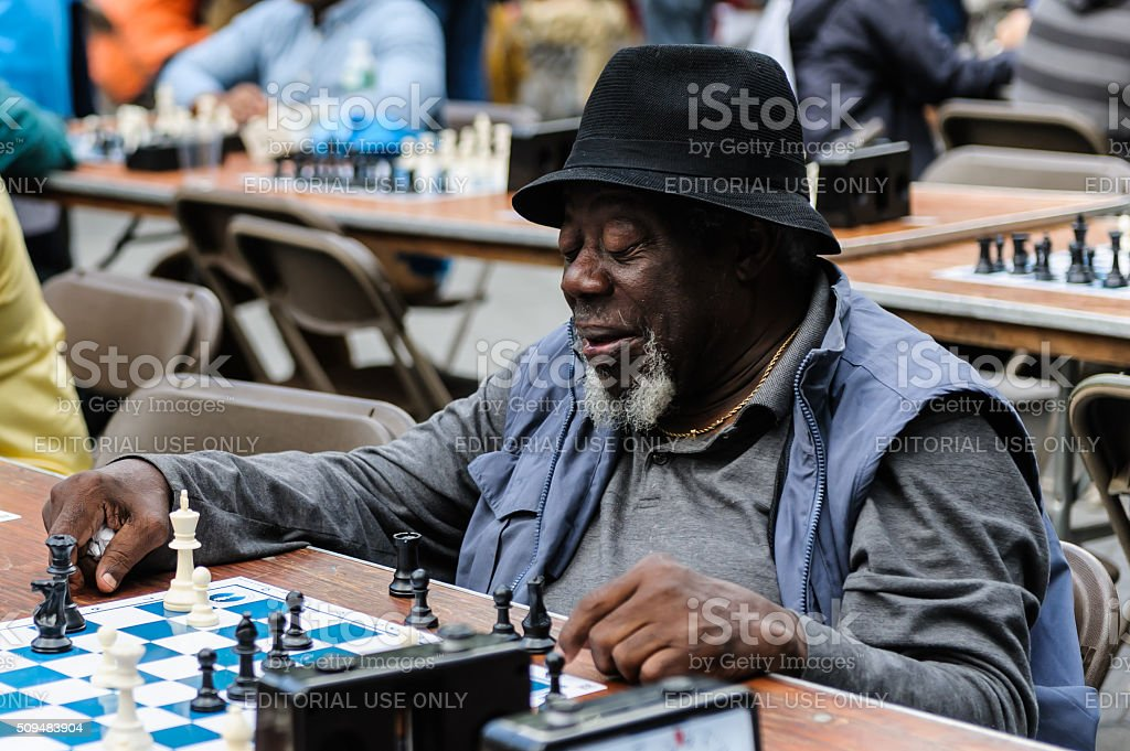 Old man playing Chess at Central Park stock photo