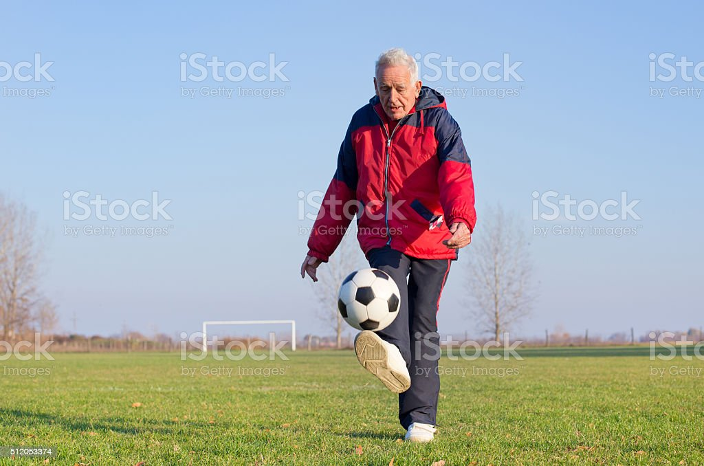 Old man playing football stock photo