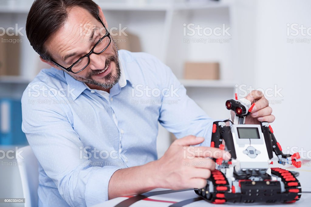 Old man playing with a robot having fun stock photo