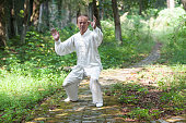 old man practice tai chi in the park