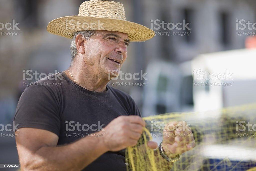 Old man preparing fishing net stock photo