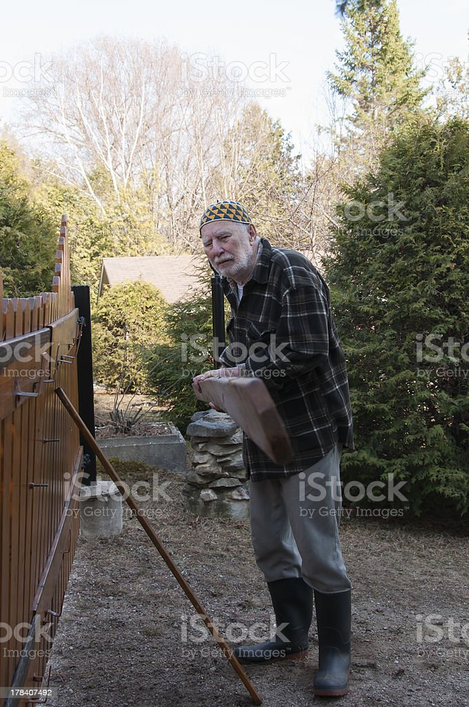 old man repairing a gate stock photo