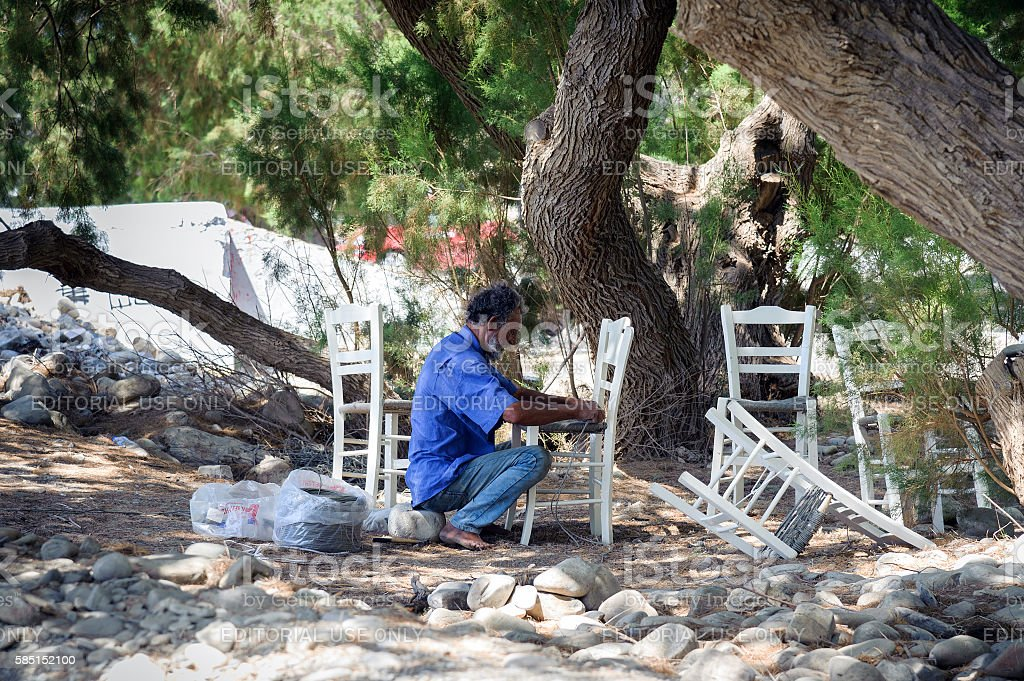 Old man repairs chairs under the trees stock photo
