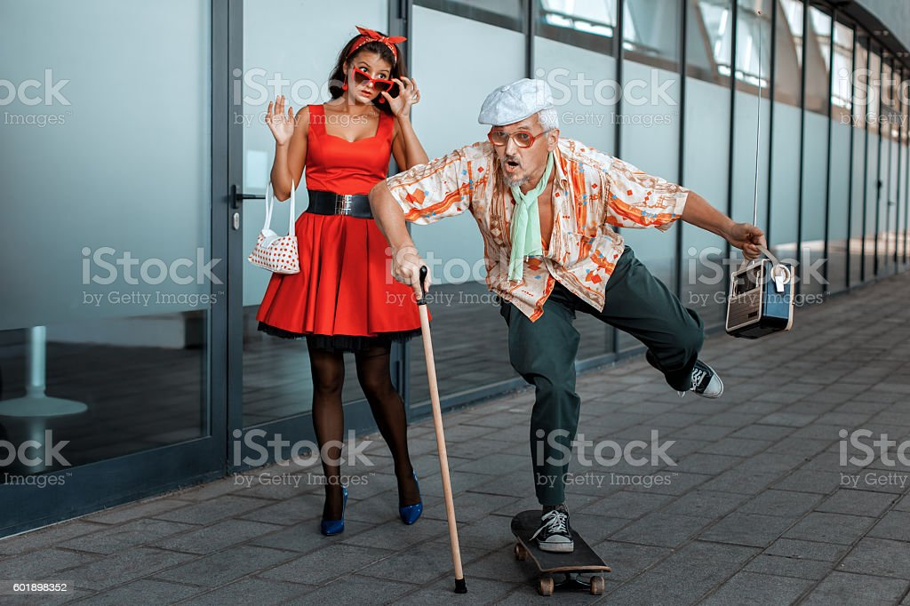 Old man ridiculously rides a skateboard, the woman has opened a mouth...