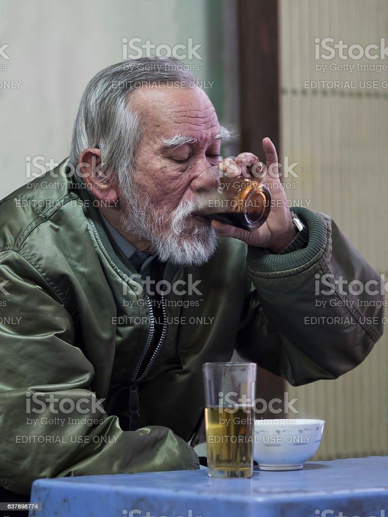 Old man savoring the intense pleasure of vietnamese coffee stock photo