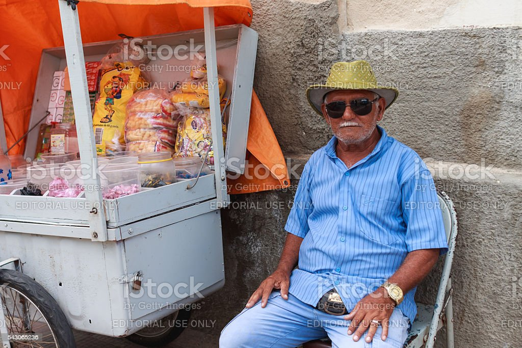 Old man sells candies in pushcart stock photo