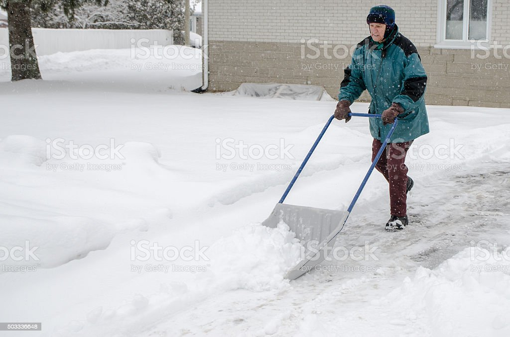 Old man shoveling snow out of his driveway stock photo