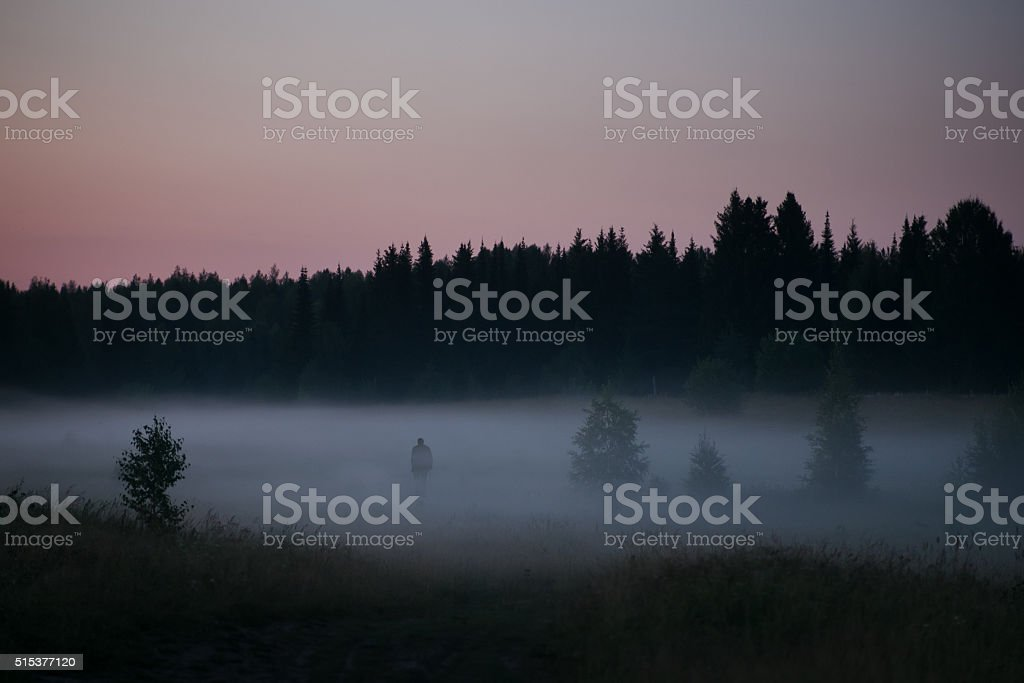 Old man silhouette at the edge of a dark forest stock photo