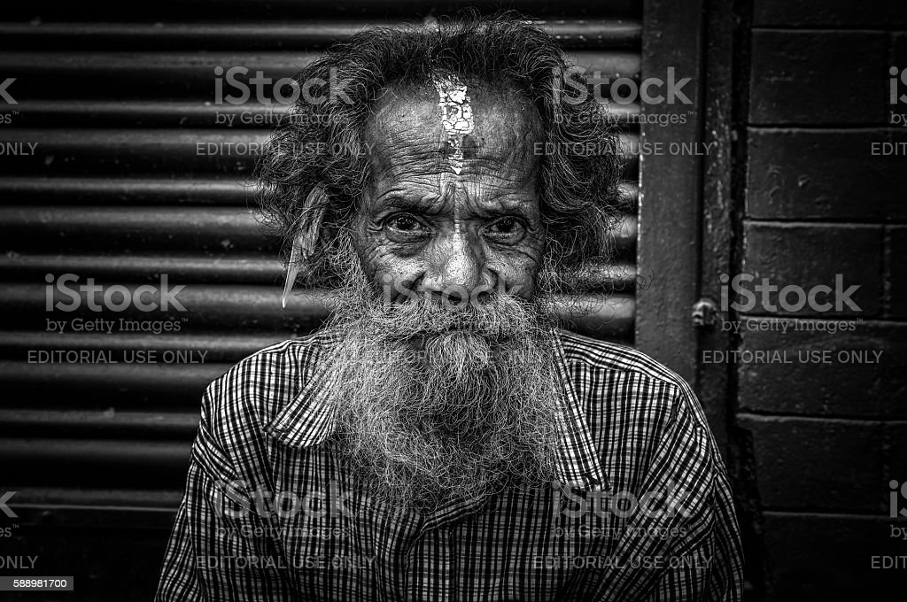 Old man sitting in the street of Kathmandu, Nepal stock photo