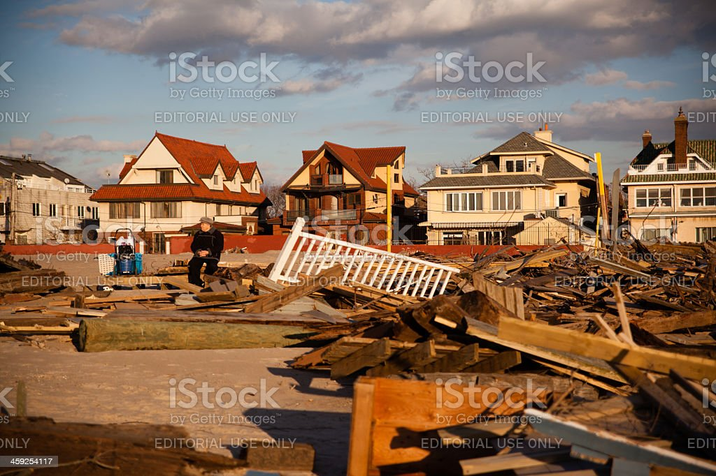 Old man sitting next to ruined homes after Sandy hurrican stock photo