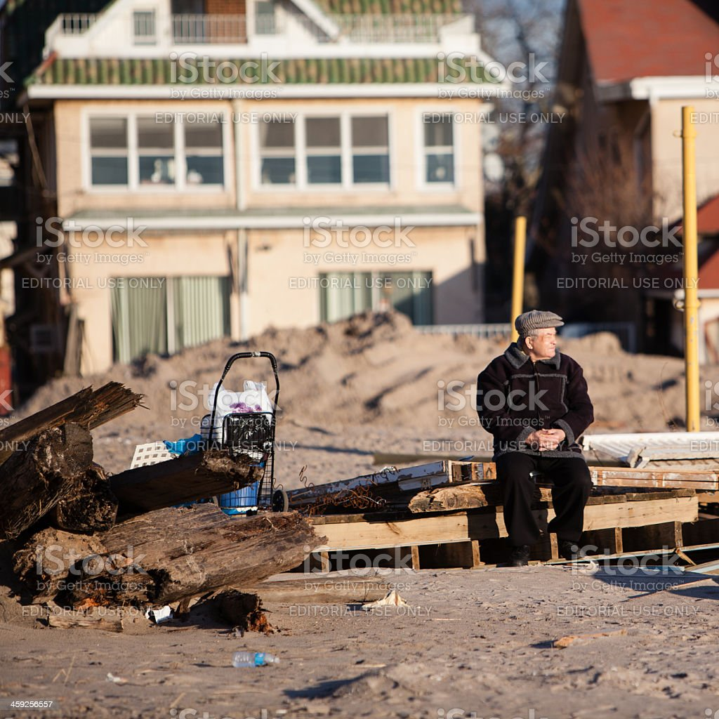 Old man sitting next to ruined homes after Sandy hurrican royalty-free stock photo