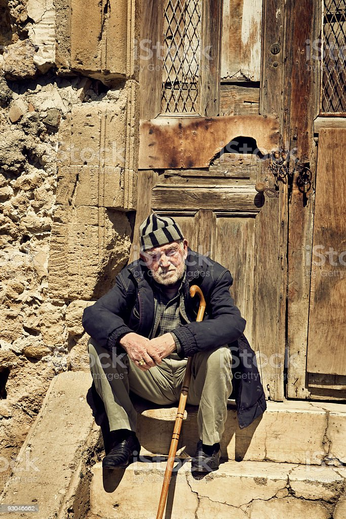 Old man sitting on the threshold of an abandoned house stock photo