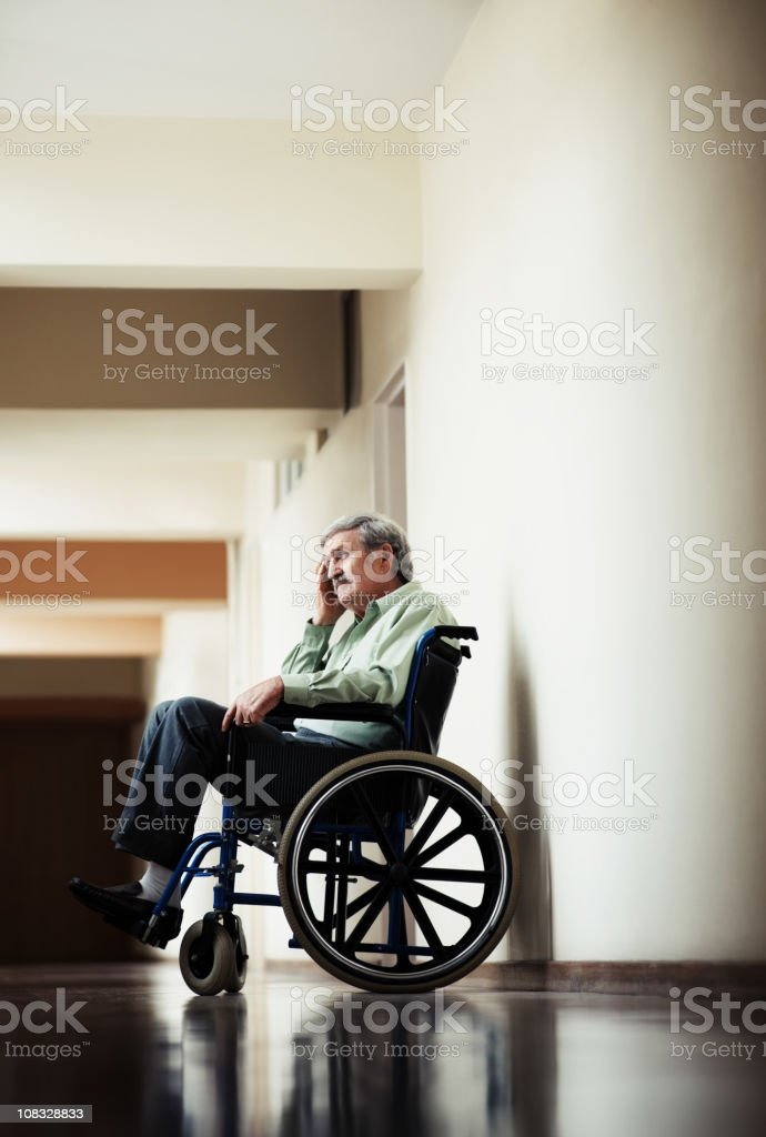Old man sitting on wheelchair in hospital corridor royalty-free stock photo