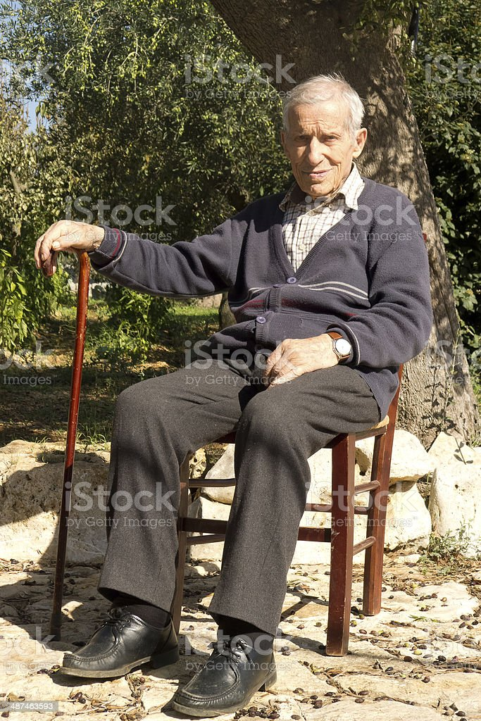 Old man sitting outdoors. stock photo