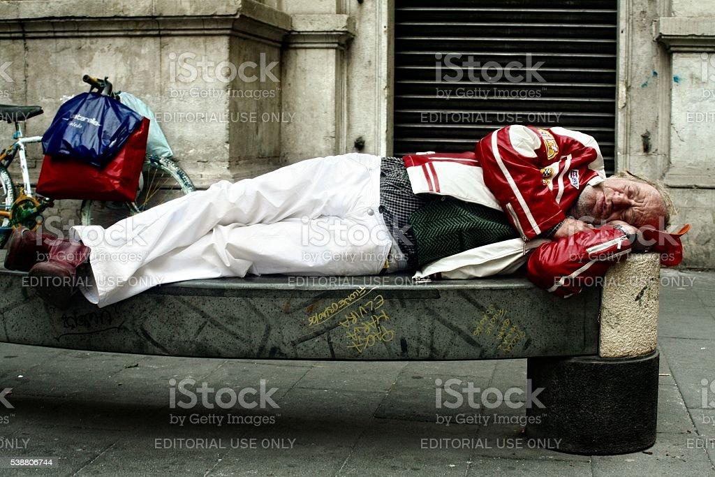 Old man sleeping on bench Naples Italy stock photo