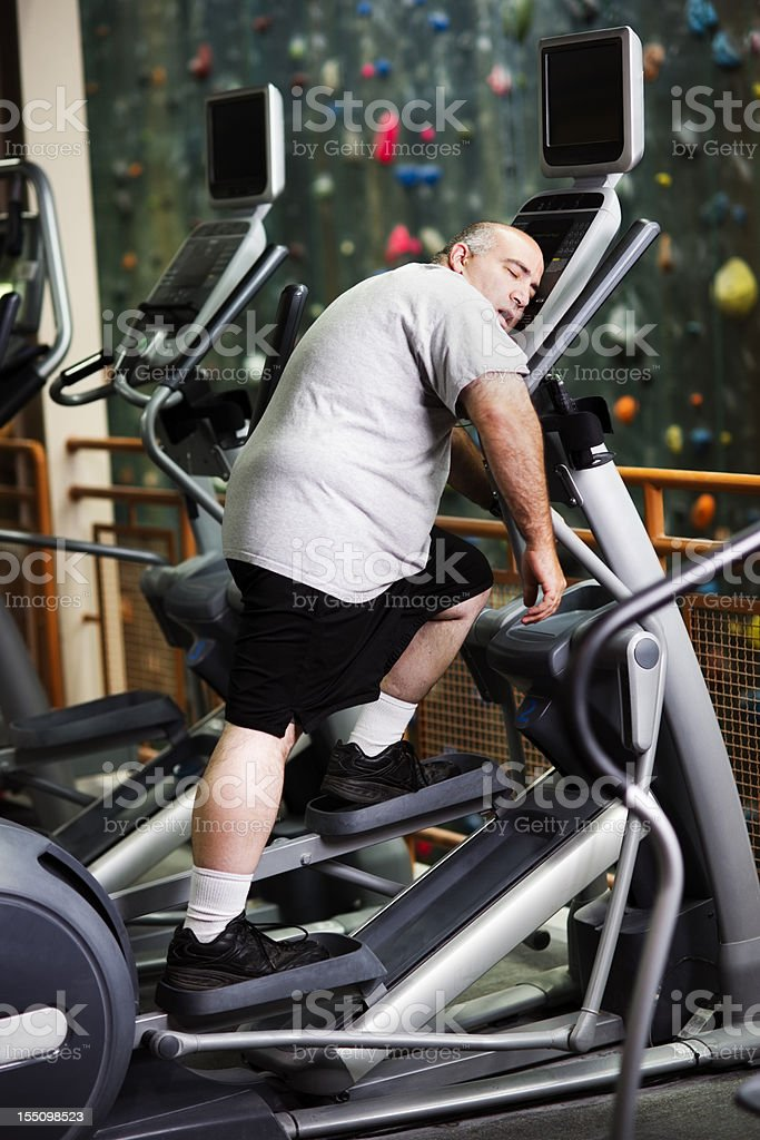 Old man slumped over a stepping machine at a gym stock photo