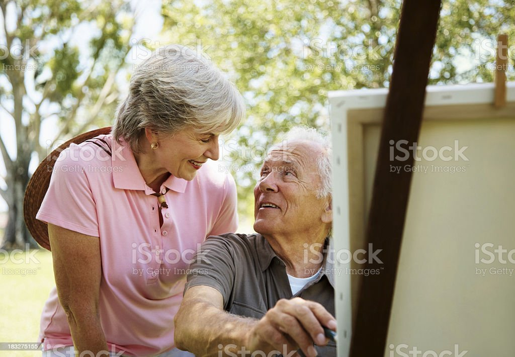 Old man smiling while painting a picture with his wife stock photo