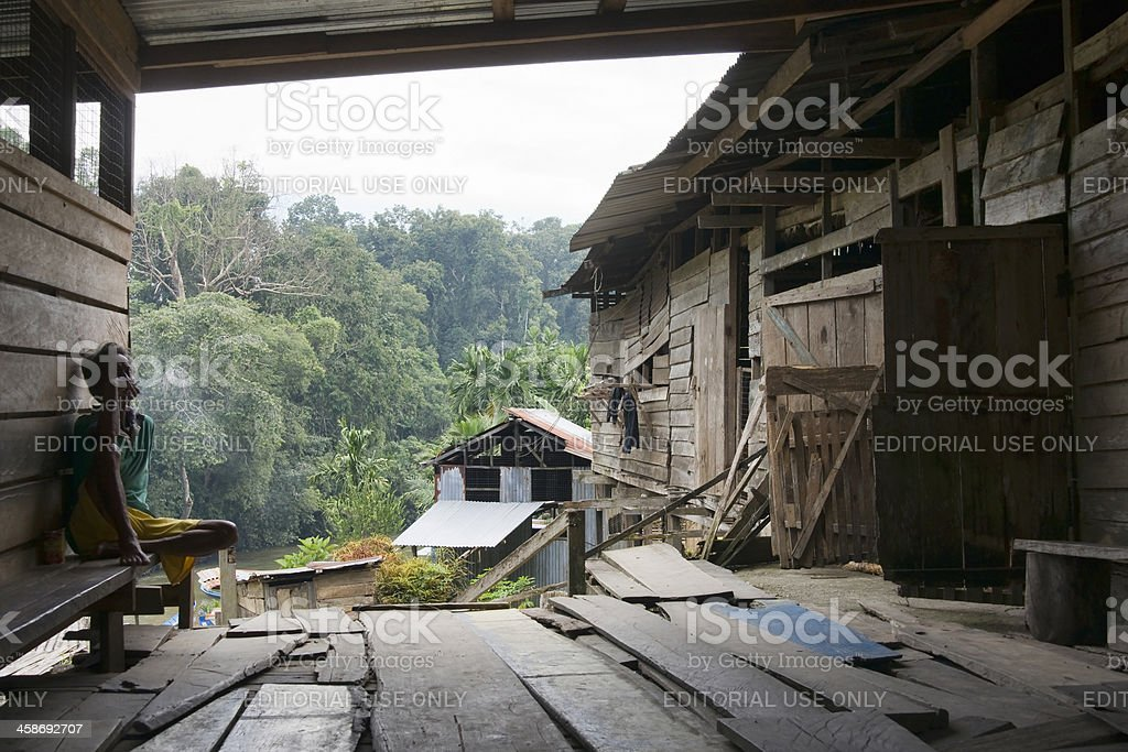 Old man smoking in the porch of a Iban Longhouse stock photo