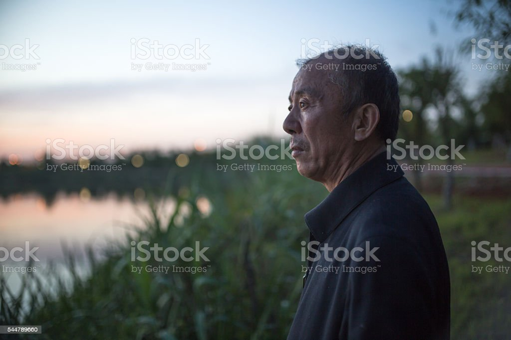 old man standing infront of lake near sunset stock photo