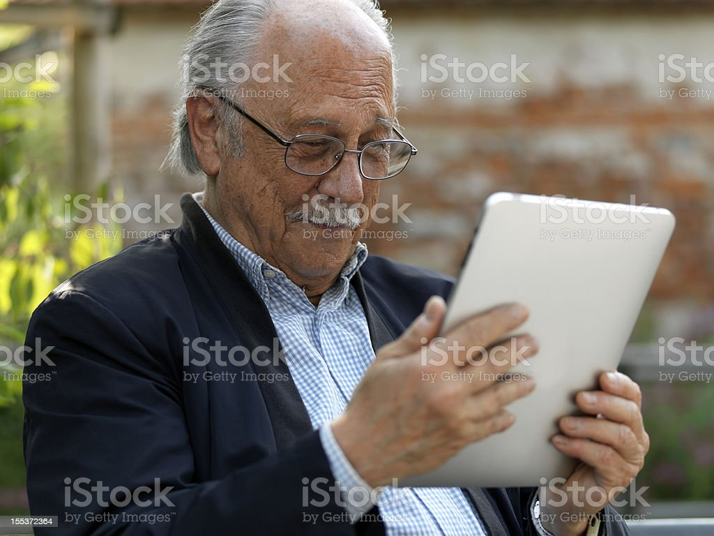 Old man tablet computer stock photo
