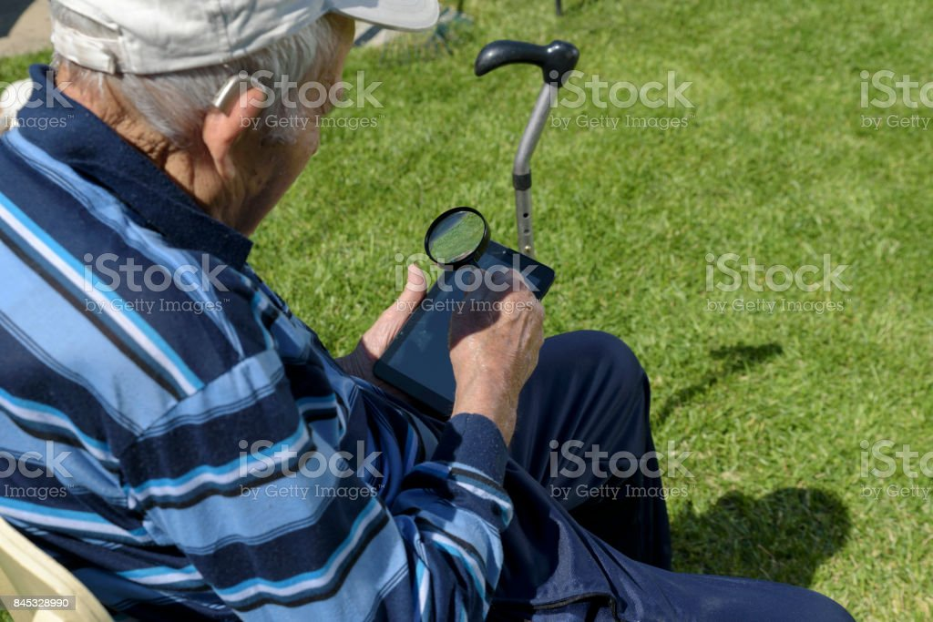 Old Man Tablet Magnifying glass Reading stock photo