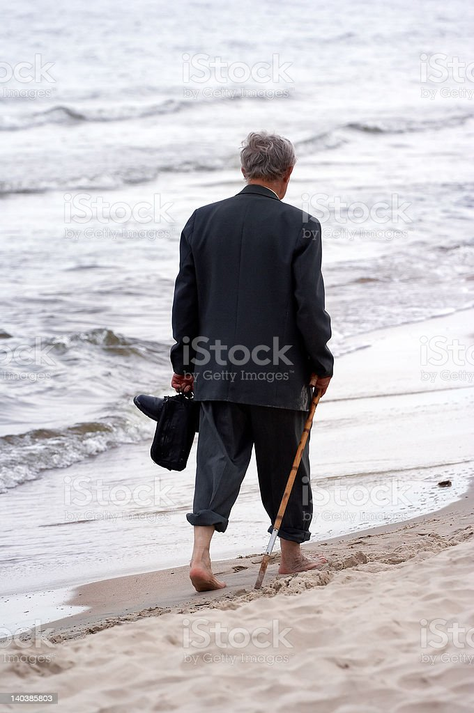 old man walking on beach royalty-free stock photo