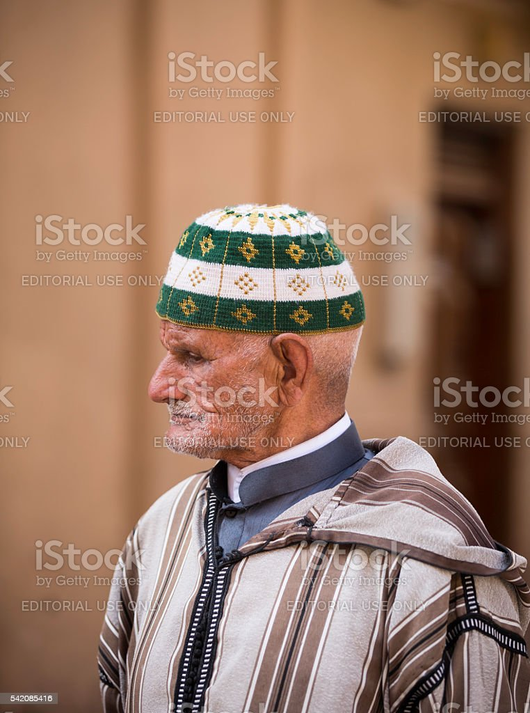 old man wearing djellaba and hat standing on the street stock photo