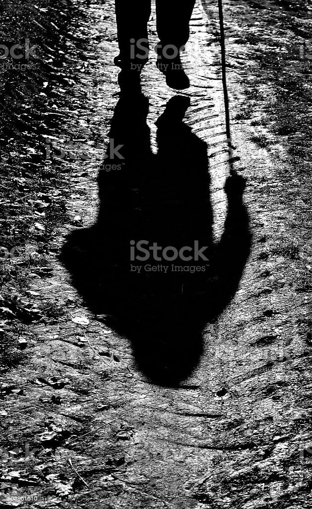 old man with a cane walking around stock photo