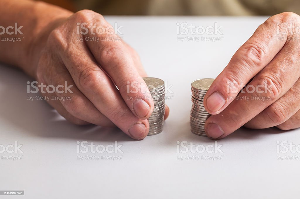 old man with coins in hand on table stock photo