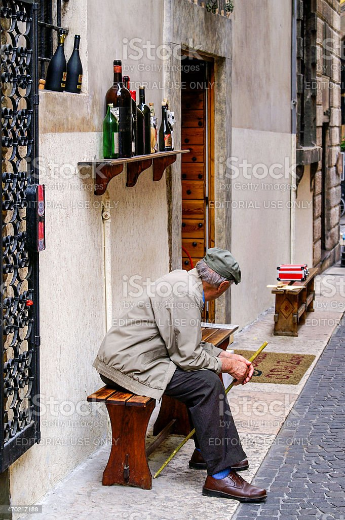 Old man with hat and cane sitting on a bench stock photo