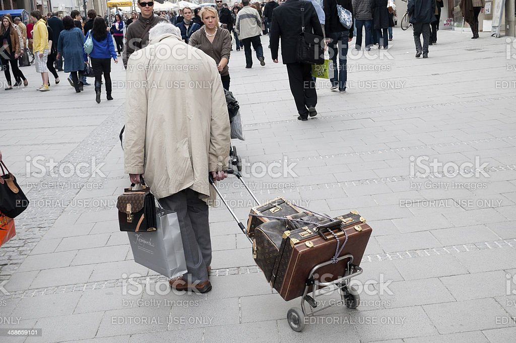 Old man with Louis Vuitton bags in Munich, Germany stock photo