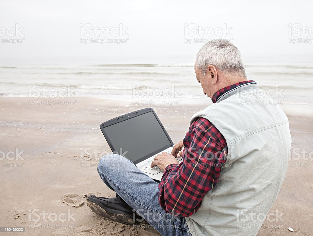 Old man with notebook on beach royalty-free stock photo