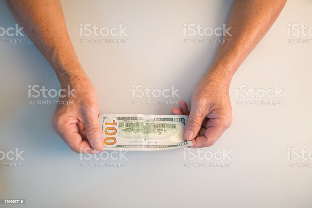 old man with one 100 dollar bill  in hand stock photo