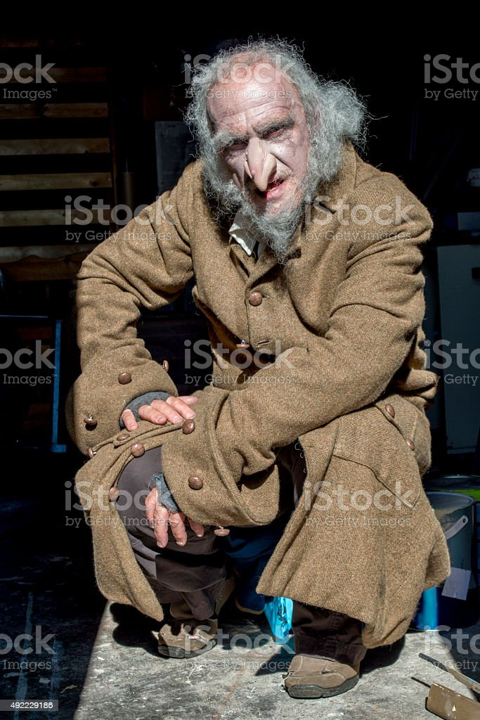Old man with scruffy appearance crouching in old room stock photo