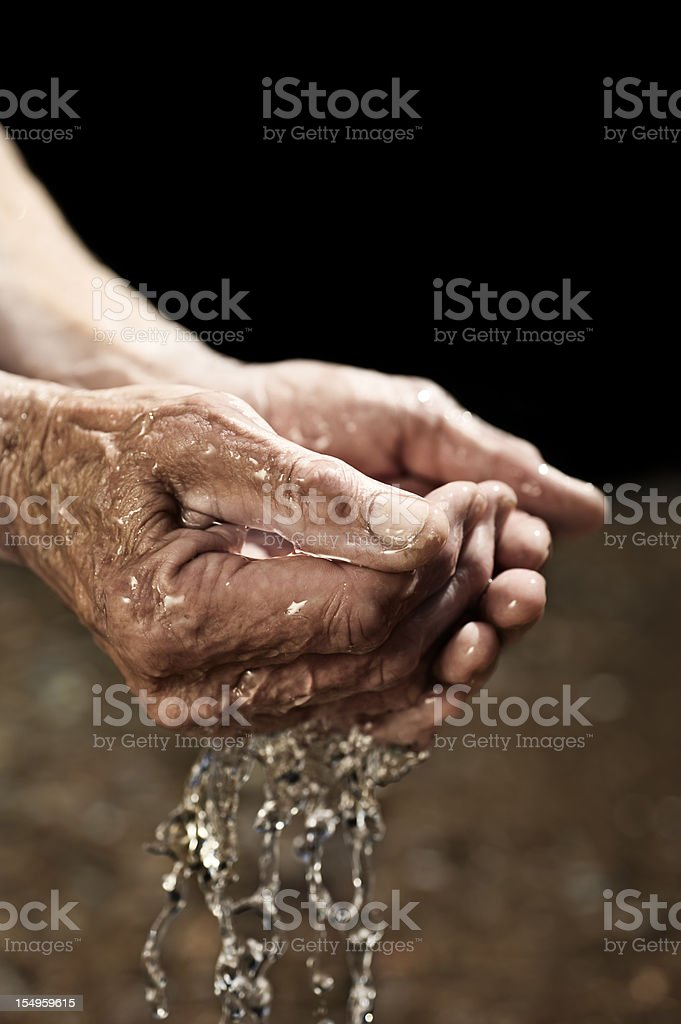 Old man's Hands cupping and drinking water stock photo