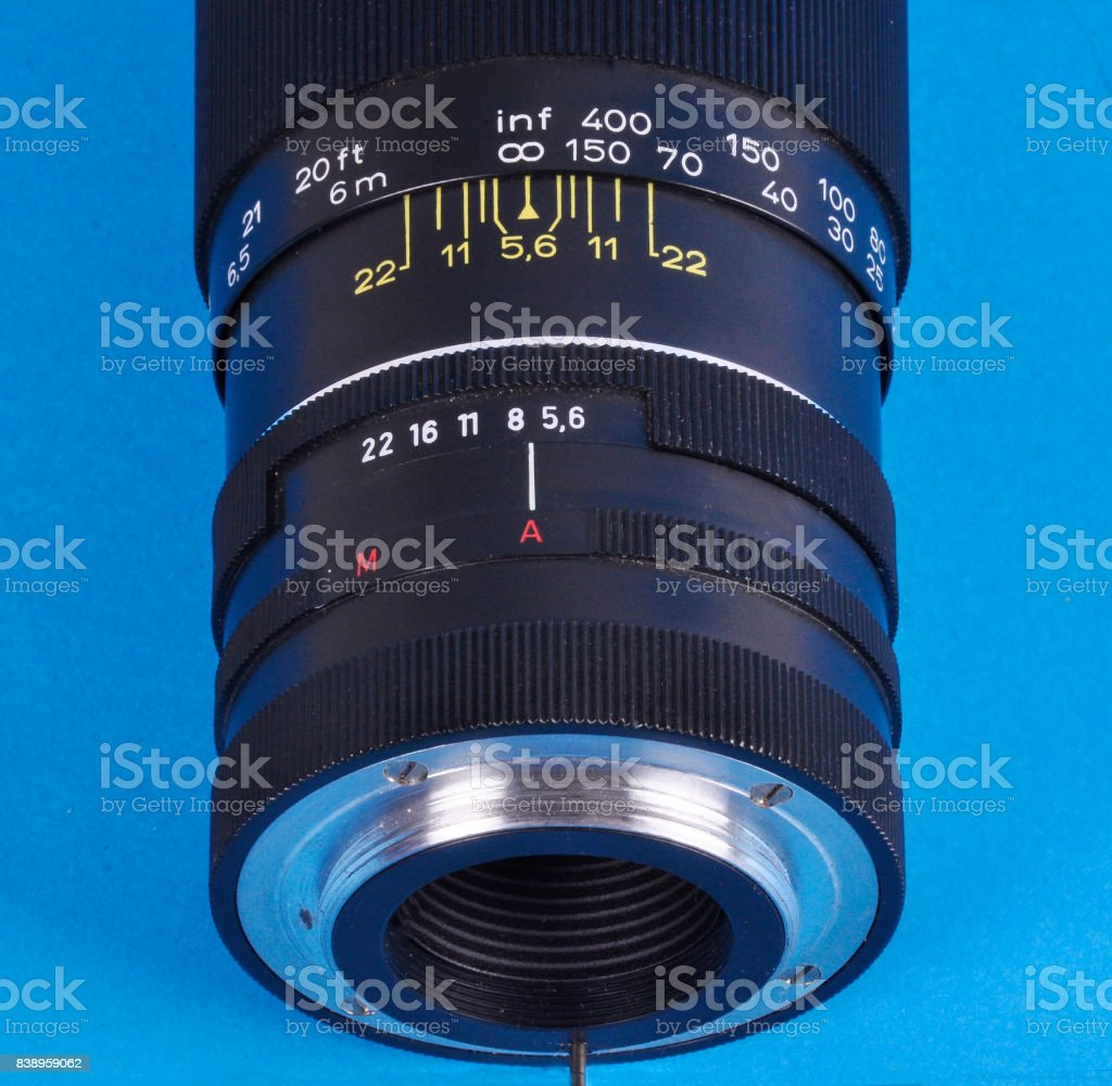 Old manual lens on a blue background stock photo