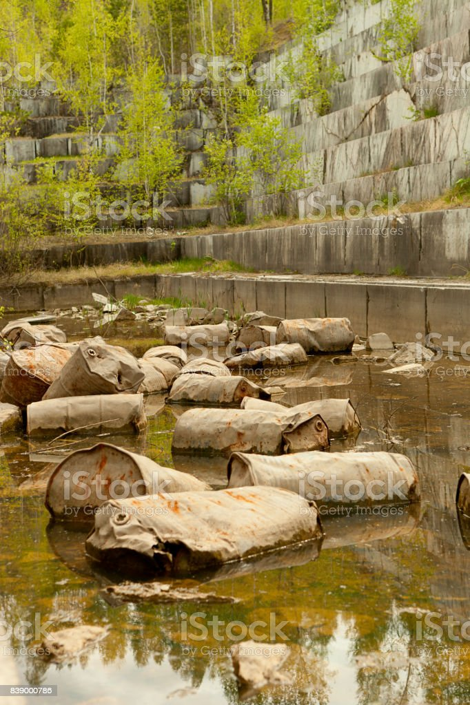 Old marble quarry, abandoned fuel barrels on bottom. Careless attitude towards nature. Industrial waste products of oil refining. Extraction of minerals by open method. stock photo