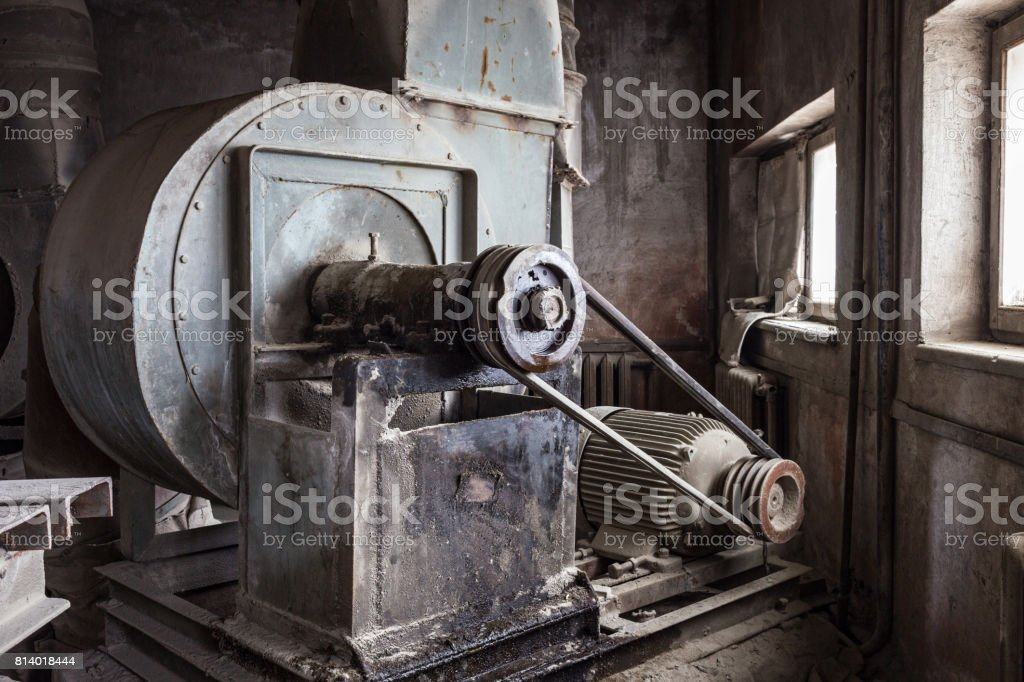 Old mechanisms covered with a thick layer of dust in an abandoned factory stock photo