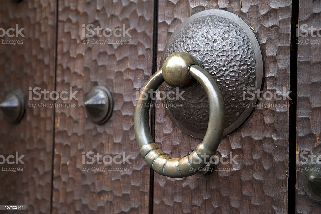 Old medieval brass knocker on antique dark wooden door royalty-free stock photo