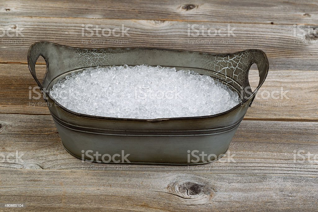 Old metal bucket filled with crushed ice stock photo