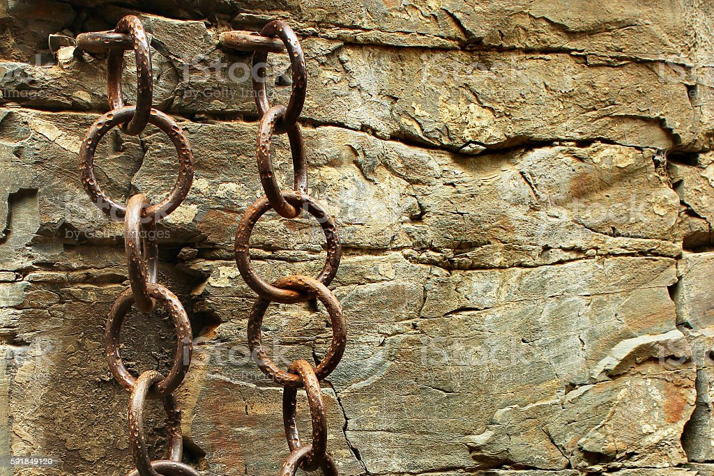 Old metal chains in the rough stone wall stock photo