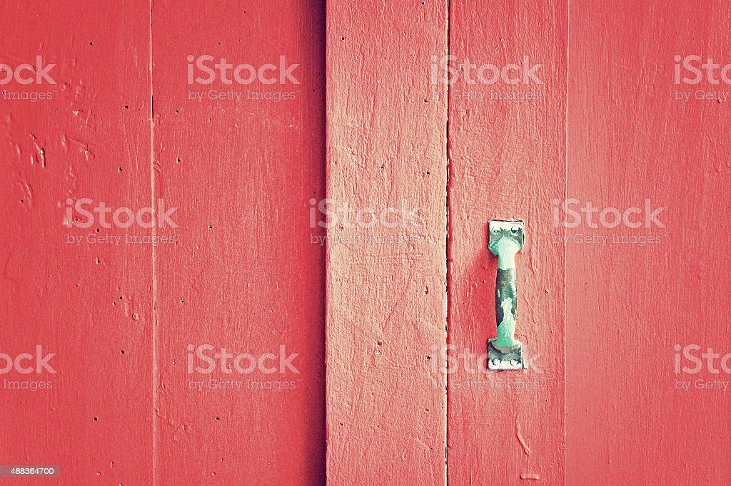 Old metal handle on red wooden door stock photo