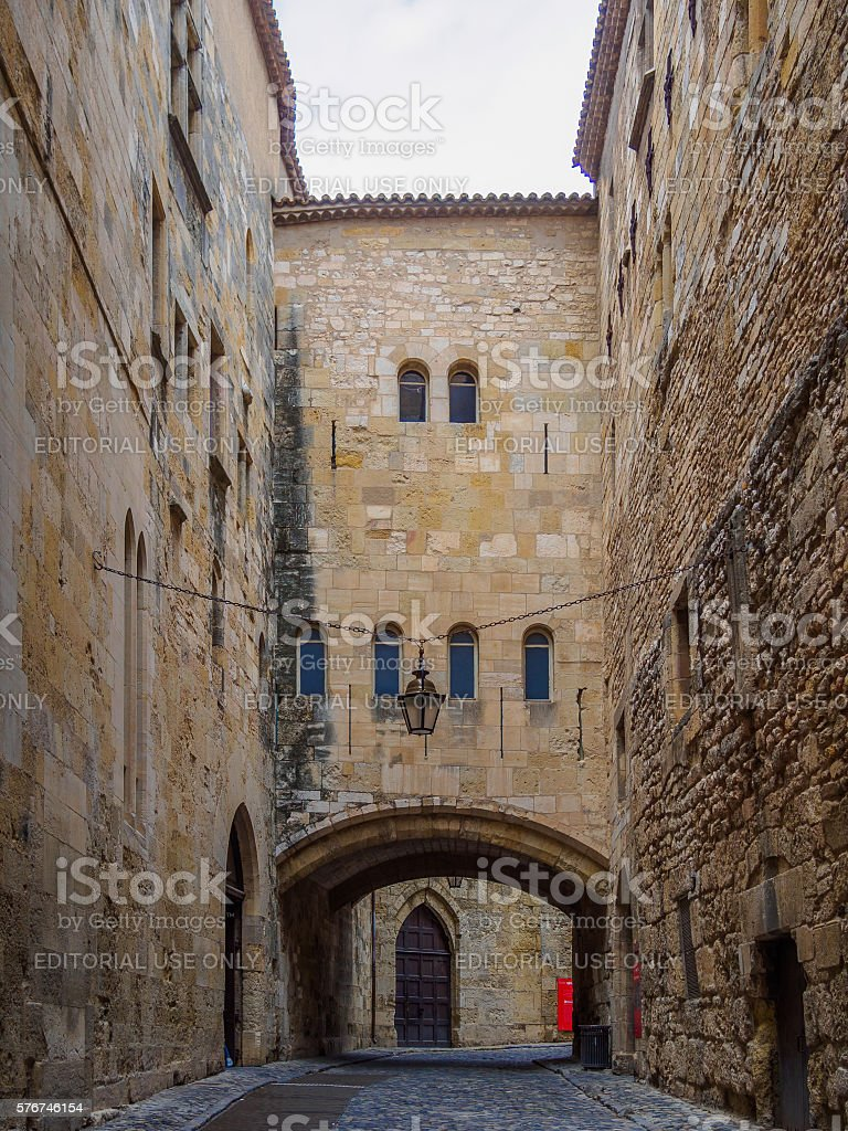 Old metal light hanging in Narbonne's medieval style stone street stock photo