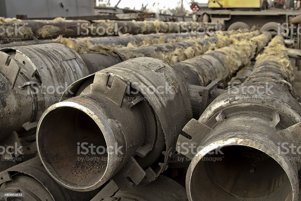 Old metal pipes are cleaned from glass wool stock photo