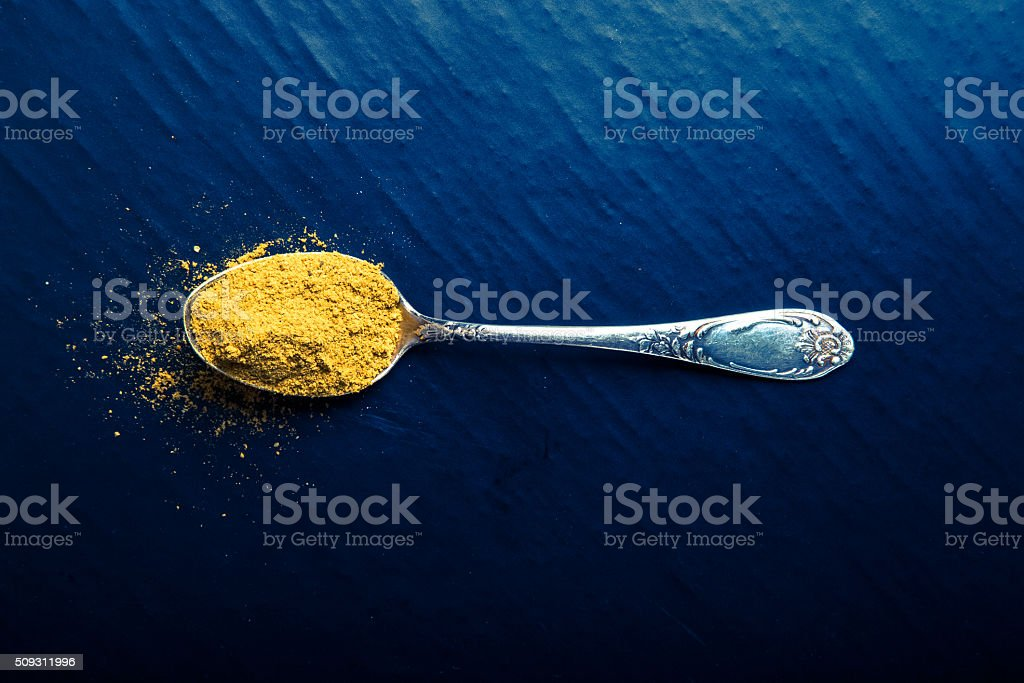 Old metal spoon with spices on a black background. Toned stock photo
